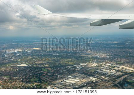 Sydney, Australia - Oct 29, 2016: Plane takes off from Sydney Kingsford-Smith International Airport. Below cloud level is the surrounding suburban districts.