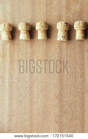 Five corks from champagne cork oak lined in a row on top of the wooden board.