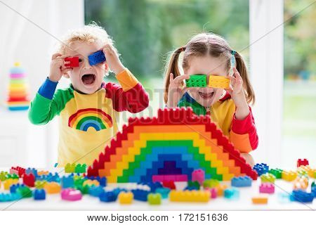 Child playing with colorful toys. Little girl and funny curly baby boy with educational toy blocks. Children play at day care or preschool. Mess in kids room. Toddlers build a tower in kindergarten. Focus on girl.