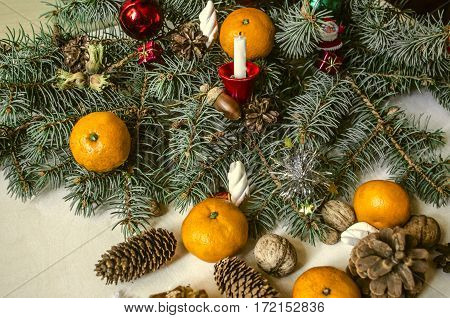 Pine branch with cones,tangerines,nuts with candle on wooden background