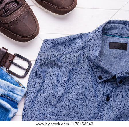 blue male jeans and shirt with brown belt and shoes, top view