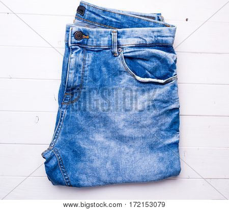 male blue folded jeans on wooden background, top view
