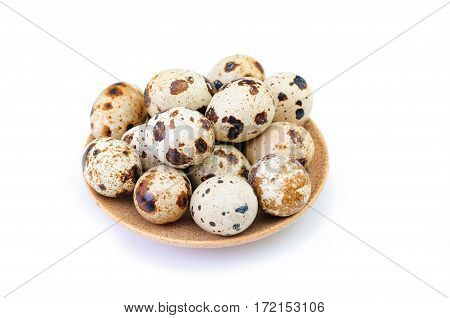 quail eggs on a brown plate isolated on white backdrop
