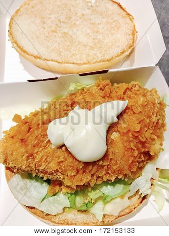 CARDIFF, UK - FEBRUARY 18, 2017:  Chicken Zinger burger with lettuce and extra mayo served in a cardboard box at KFC, Cardiff, Wales, UK