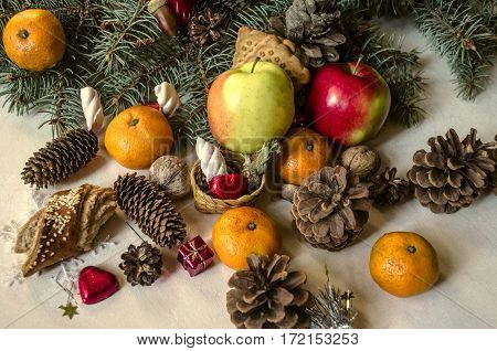Fruits, nuts, pastries, chocolates with various coniferous cones and spruce branch on light wooden table