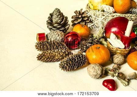 Straw basket with fruit,mandarins,chocolate,cones and nuts on light wooden table