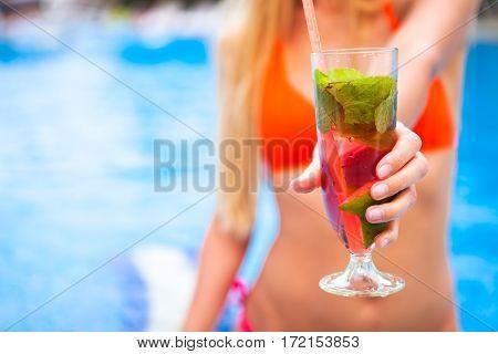 Woman In Bikini Hand With Cocktail Glass Strawberry Mojito Near Swimming Pool. Close Up