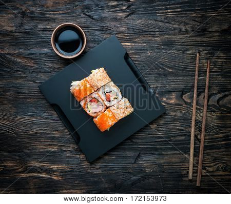 set of sushi rolls with soy and chopsticks on black wooden background top view