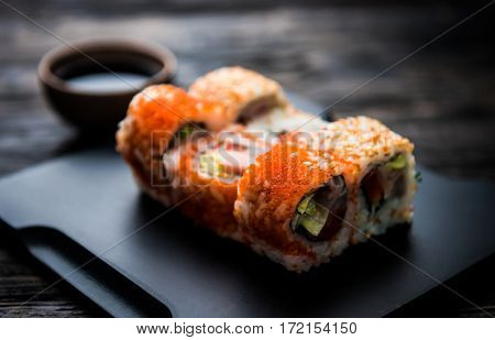 close up of sushi rolls on black tray and dark wooden table