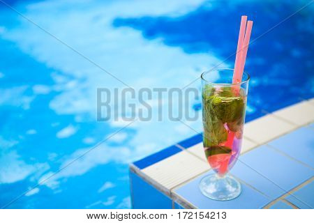 Glass of refreshment drink on a pool side close up