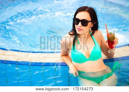 Tanned Beautiful Woman In Bikini And Sunglasses Sitting In Swimming Pool With Cocktail. Fashionable