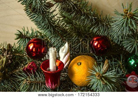 Red and green Christmas balls with candle and tangerine on conifer branch