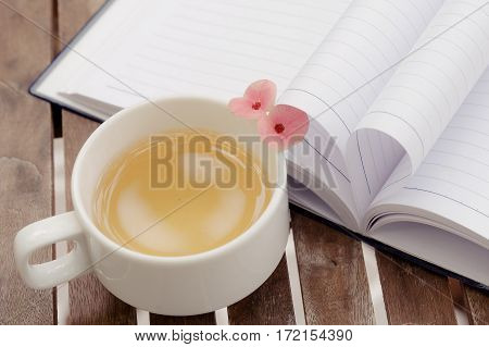 Couple of Crown-of-thorns flower and a cup of tea on wooden table with heart shape which made by white paper notebook. Vintage color.