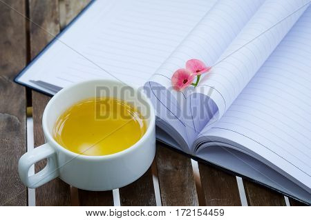 Couple of Crown-of-thorns flower and a cup of tea with heart shape which made by white paper notebook