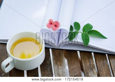 Couple of Crown-of-thorns flower and rose leaves & a cup of tea with heart shape which made by white paper notebook