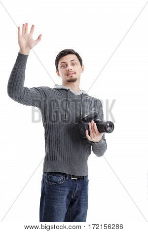 young successful professional photographer in shirt with DSLR digital camera waving Hello isolated on white background