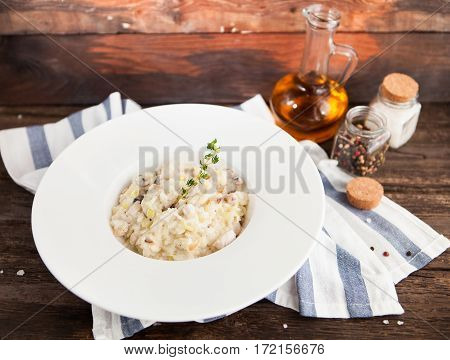 Risotto With Mushrooms And Chicken On A White Plate On A Wooden Background