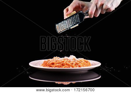 Rub grating Parmesan cheese on pasta spaghetti macaroni plate. Hands grate cheese on black background