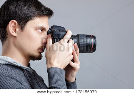 profile portrait of young successful professional photographer in shirt use DSLR digital camera on grey background