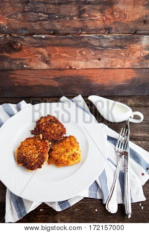 Hash Brown Potato Cakes With Creamy Sauce On A Wooden Background