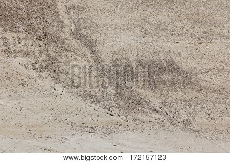 Arid dry cracked yellowish soil slope with small stones and little vegetation