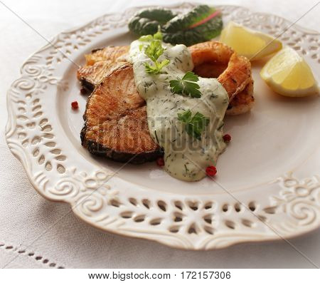Grilled salmon steak with sauce and herbs