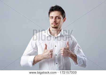 portrait of handsome young smiling Brunet man in white shirt showing thumbs up gesture on gray background.