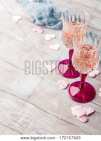 Two stemmed champagne glasses with pink hearts on wooden textured background. Valentine's day wedding romantic date invitation