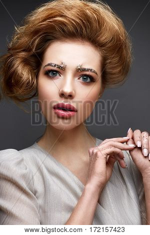 Young girl with lush hairstyle and make-up Nude. Beautiful model with sequins on the eyebrows and gentle pink manicure. The beauty of the face. The photo was taken in studio
