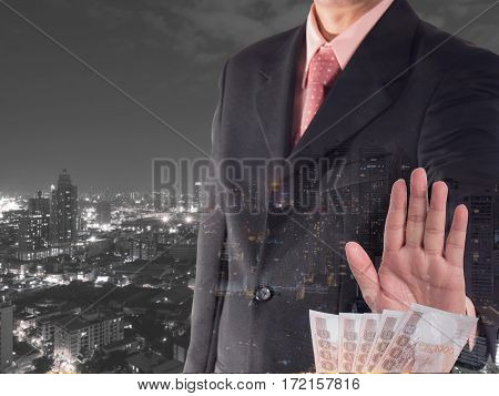 Double exposure of businessman decline a bribe with cityscape night light background. Stop corruption and fraud concepts