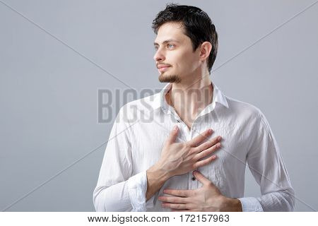 handsome young proud man in a white shirt holding hand on chest on grey background.
