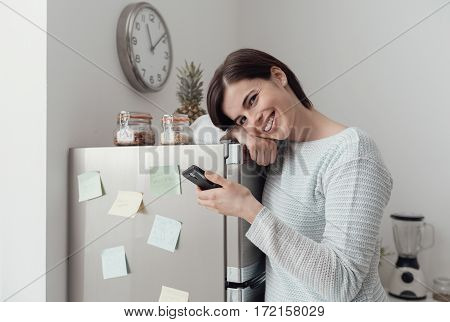 Woman Texting In The Kitchen