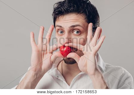 handsome young brunette man in white shirt holds in hands a red heart and fool around on a gray background. soft light
