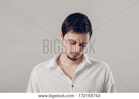 handsome young frustrated and resentful brunette man in white shirt on gray background. soft, light