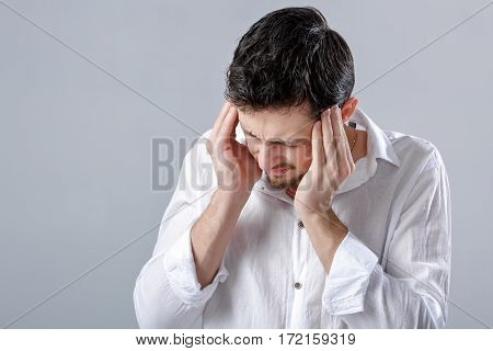 Frustrated young brunette man in a white shirt with headache on  gray background. terrible migraine