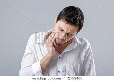 Frustrated young brunette man in a white shirt with toothache on gray background.