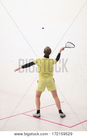 back view of squash player hitting a ball in a squash court. Squash player in action. Man playing match of squash