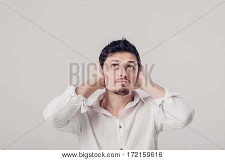 portrait of a young Brunet man in white shirt covers his ears with his hands against a grey background. I don't want to hear anything. soft light