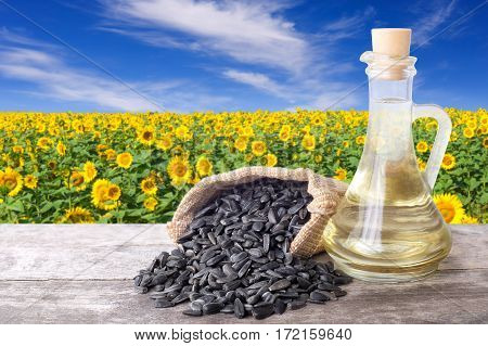 Sunflower oil in glass bottle and seeds on wooden table with blossom field on the background. Sunflower field with blue sky. Photo with copy space area for a text
