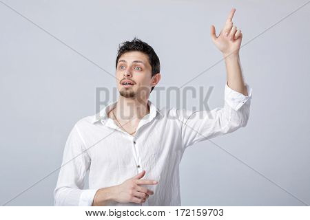 young man with an idea raising his finger in the air on gray background. gesture Eureka