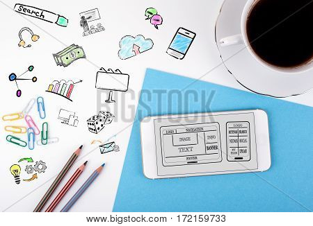 Website and mobile app development Concept. Mobile phone and coffee cup on a white office desk.