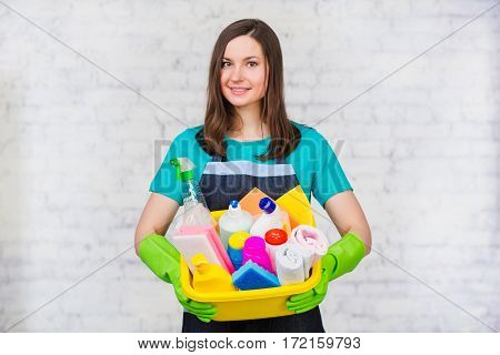 Young woman cleaner holding bucket with many colorful detergent for cleaning Home. Worker cleaning service. On the soft-focus background a white brick wall