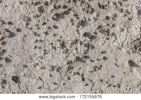 White arid cracked dry textured desert soil with brown black pebbles
