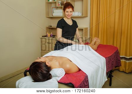 Massage therapist massaging a female body, standing in the spa salon and looking at camera. Wellness for beautiful body