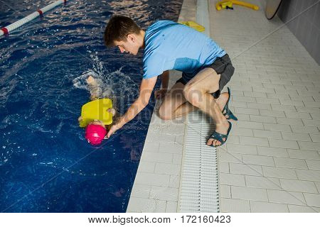 Children's swimming coach trains the girl. learning to swim using kickboard at swimming pool