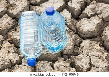 bottle with water on the dried ground close up. Global drought, warming.