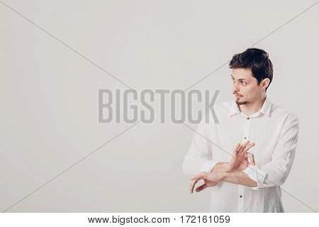 portrait of attractive young brunette man in white shirt adjusting his sleeve on a grey background. soft light