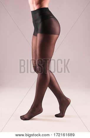 Female Legs In Black Pantyhose On Gray Background