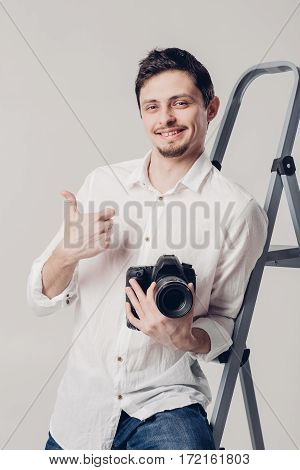 young successful professional photographer in shirt use DSLR digital camera on grey background. soft light