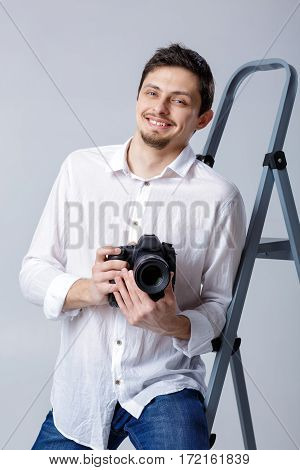 young successful professional photographer in shirt use DSLR digital camera on grey background